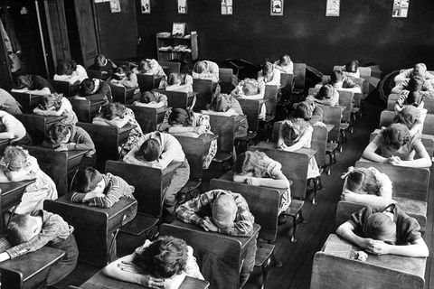 Elementary school children with heads down in a classroom
