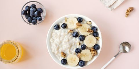 what to eat during periods for energy oatmeal porridge with walnuts, blueberries and banana in bowl on pink   healthy organic breakfast, oats with fruits, honey and nuts