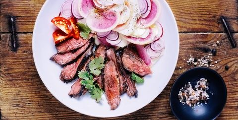 what to eat during your period for energy a sliced steak with fresh salad on a plate on wooden background