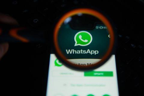 WhatsApp logo is seen trough a magnifying glass on an...