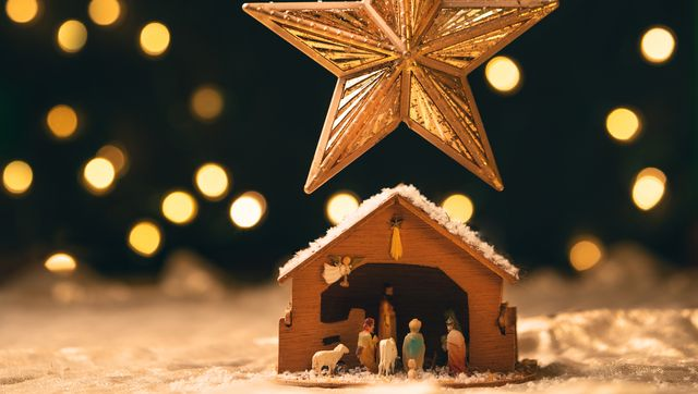 a manger sitting under a star ornament that is hanging from a christmas tree with lights blurred behind