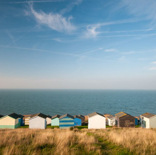 colourful holiday wooden beach huts facing the calm atlantic sea agains a blue cloudy sky  whitstable at kent great britain