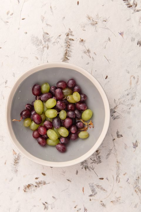 White and crimson grapes in grey bowl.