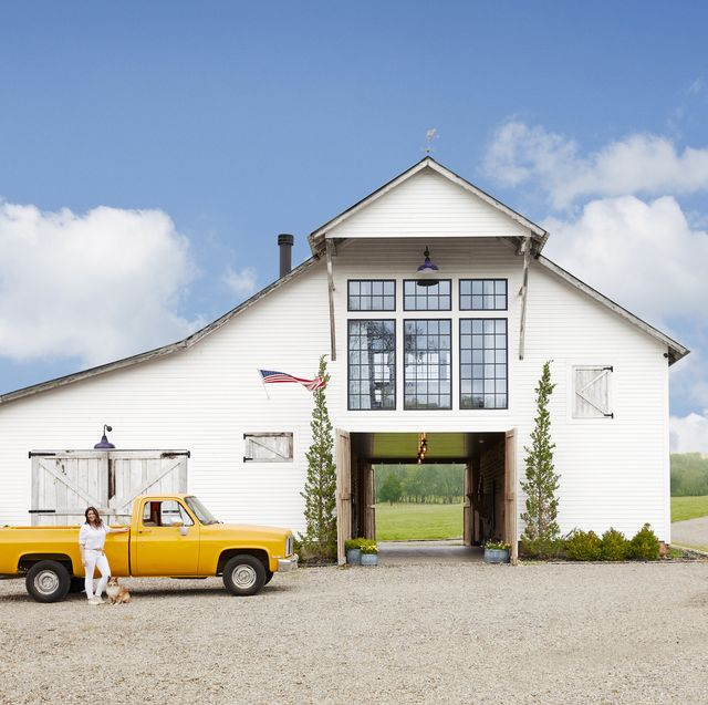 white converted barn home with yellow truck in front