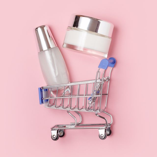 white cosmetic jars with cream lie in a shopping trolley on a pink background