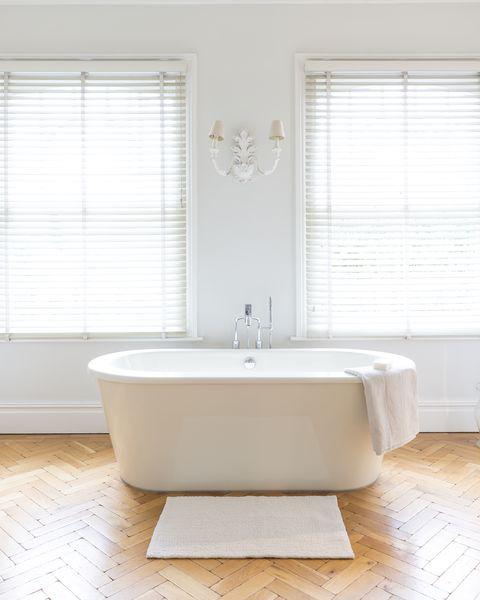 White, luxury home showcase bathroom with soaking tub and parquet hardwood floor