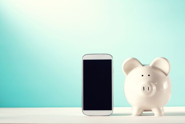 white piggy bank with a smart phone