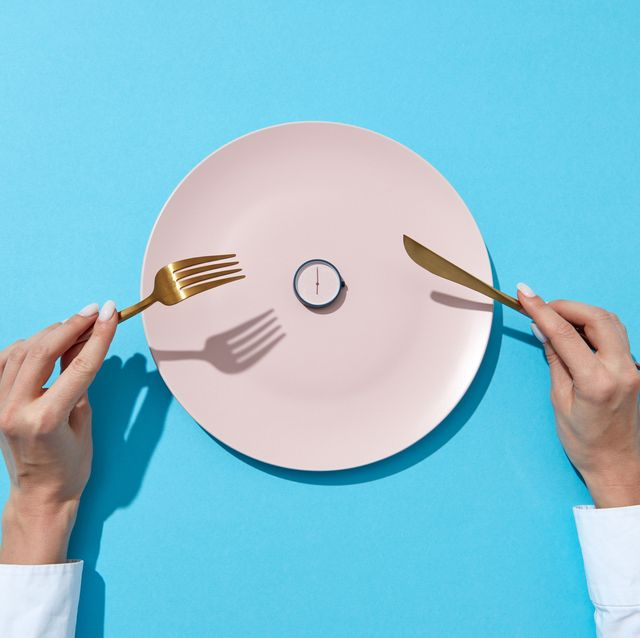 white plate with round whatch shows six o'clock served knife and fork in a girl's hands on a blue background time to eat and diet concept top view