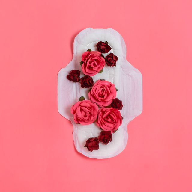 white sanitary pad with red and pink flowers on it, woman health or body positive concept pink background  flatlay copyspace