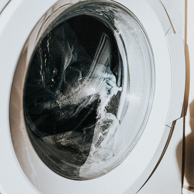 close up on a white washing machine with a glass front, as clothing spins around mid cycle the glass casts a shadow on the wall, with space for copy