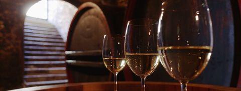 White wine in glasses on wine cask