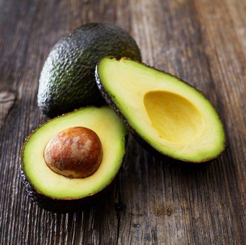 Whole and sliced avocado on wood