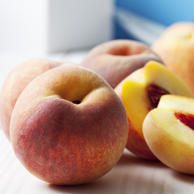 whole and sliced peaches on white wooden table