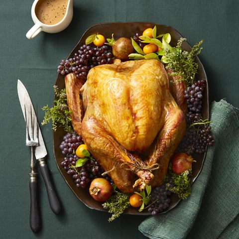 whole roast turkey on platter with garnishes and green tablecoth