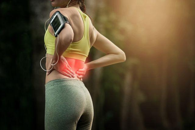 corredora joven con dolor de espalda
