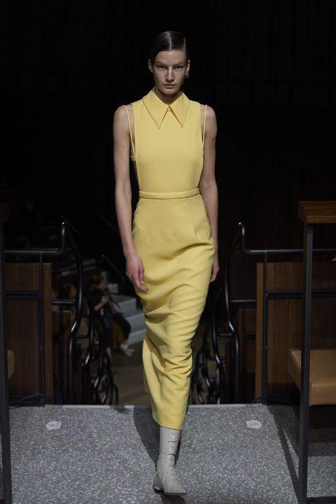 Fashion model, Fashion, Fashion show, Runway, Clothing, Fashion design, Yellow, Dress, Shoulder, Haute couture,