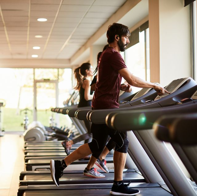 wide angle view of three people running at the treadmill