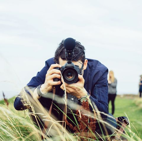 man photographing through slr camera on hill against sky
