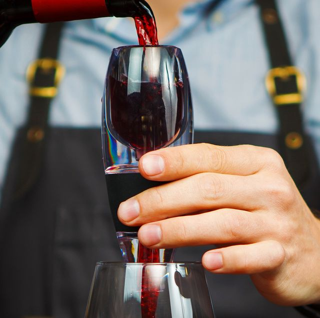 man in apron pouring red wine through an aerator