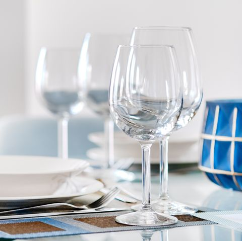 table setting with empty wine glasses, white plates bowls and flatware served on table close up of tableware, dishes, nobody preparation for dinner and guests reception
