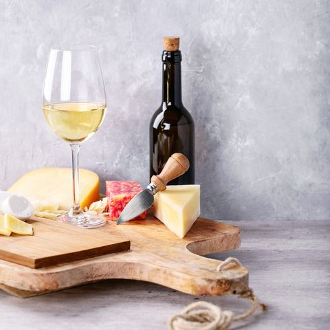 Wine With Cheese On Table Against Wall