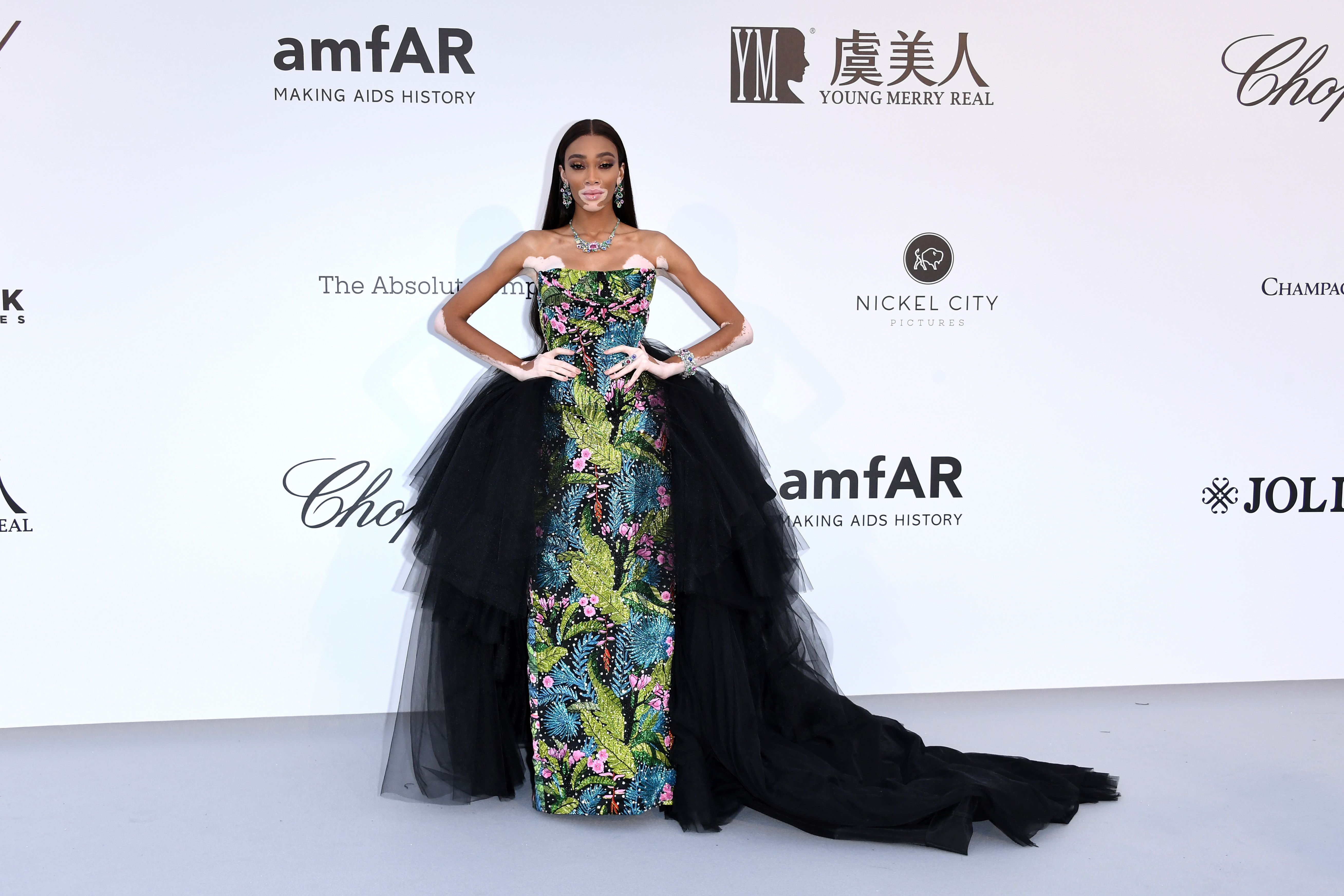 Winnie Harlow In a strapless blue and green print dress with a tulle black skirt.