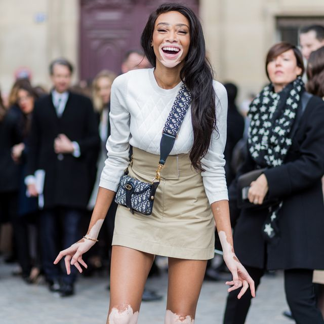 paris, france   march 03 model winnie harlow wearing white knit, mini skirt, boots, dior bag outside dior on march 3, 2017 in paris, france photo by christian vieriggetty images