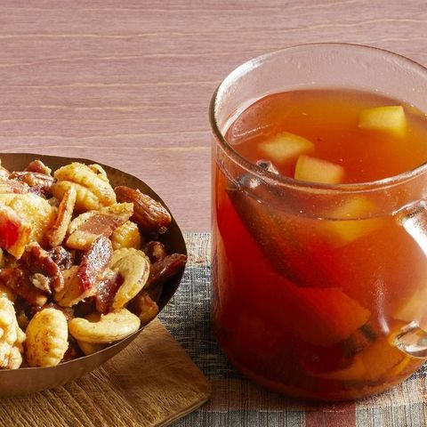mulled cider with bourbon in glass mug with bowl of nuts