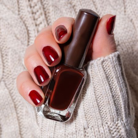 beautiful young woman hand with brown nails polish holding the small bottle with color for a manicure woman hand on white woolen sweater background manicure and beauty concept close up, selective focus fashion and femininity image