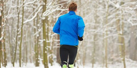 Guy running on a snow covered trail in the winter