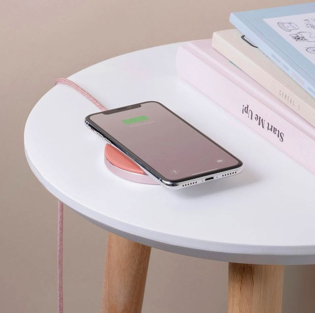 phone resting on native union wireless charger on side table with books