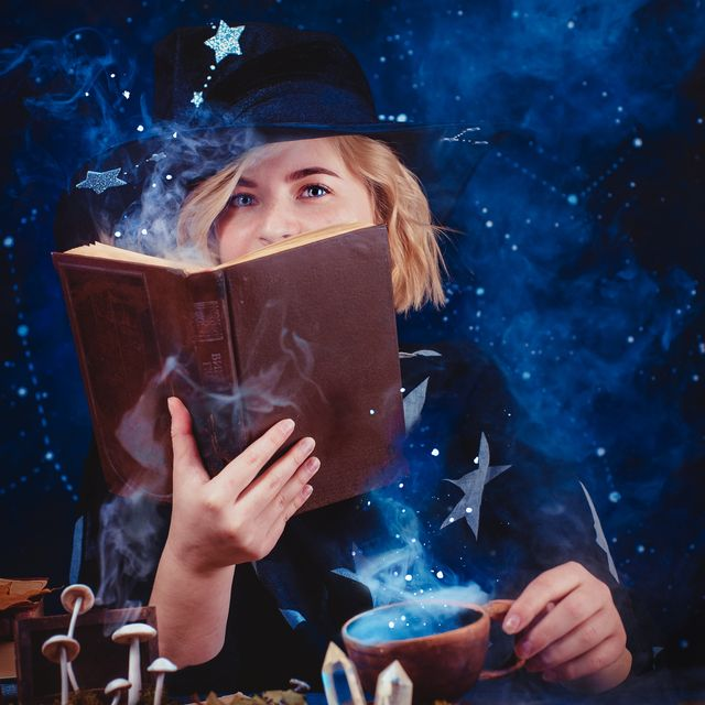 charming young witch with a book of spells and magical potions magical workplace with candles, mysterious smoke, crystals and mushrooms dark background with stars and copy space