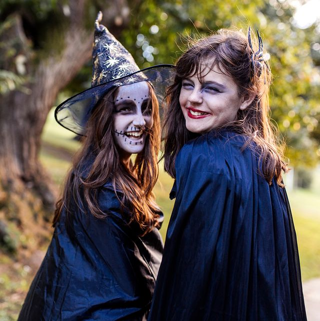 girls in halloween costumes with witch hat and makeup