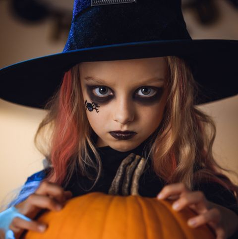 portrait of little witch halloween with a spider painted on her face