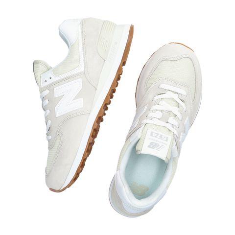 beige en witte sneakers met logo van new balance via omoda