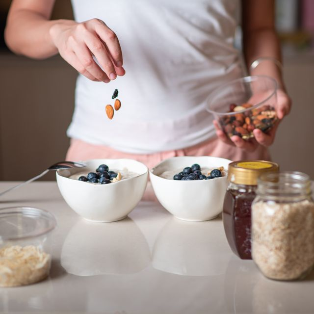 woman adding nuts into morning oatmeal cereals porridge for making a healthy and nutritious breakfast at home