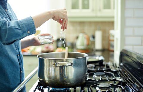 Femme ajoutant du sel à la marmite sur la cuisinière