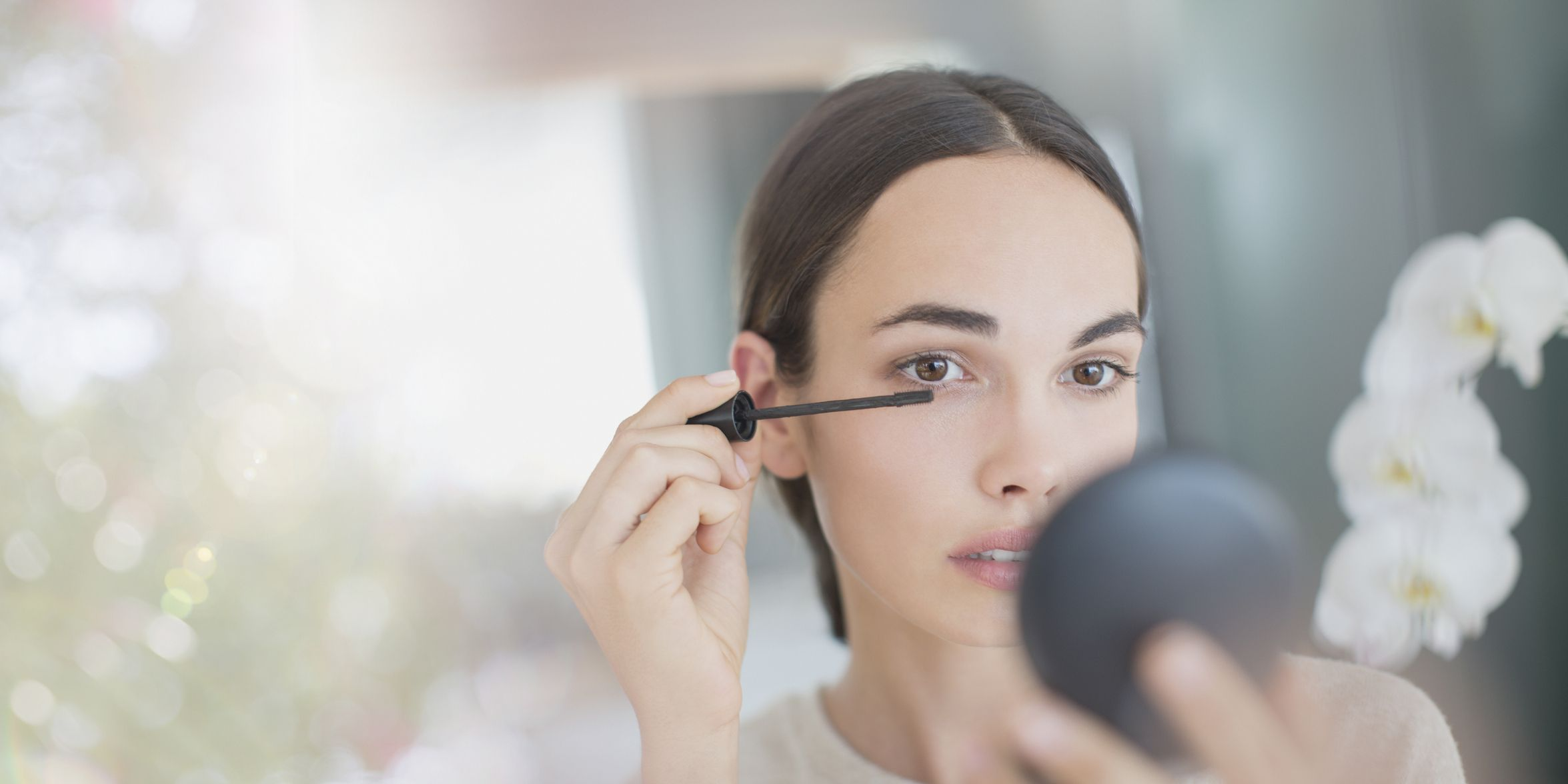 Woman apply mascara with mascara wand and compact mirror