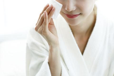 Woman applying cleansing lotion to face, using cotton wool pad