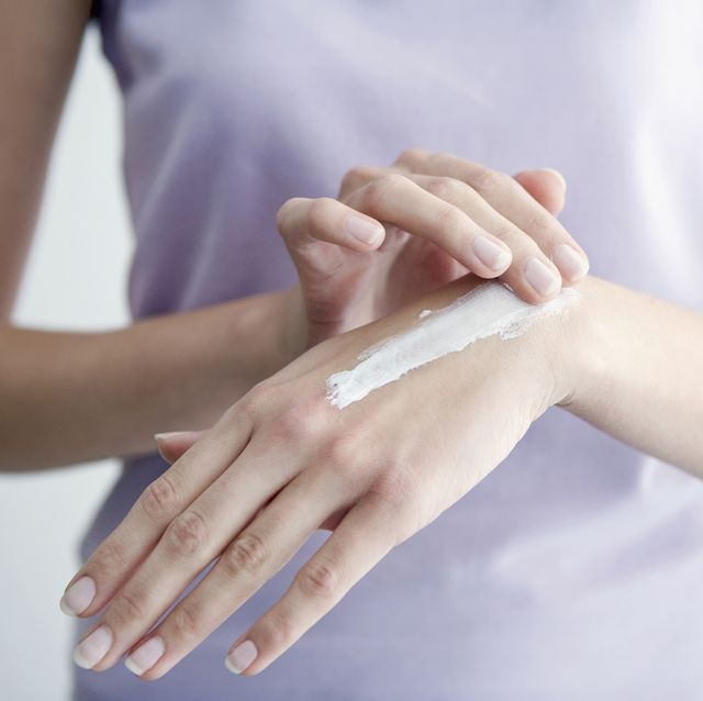 woman applying cream to hands, close up