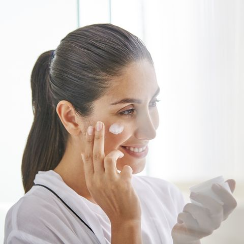 Woman applying face cream to cheek