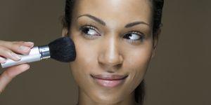 A woman applying face powder