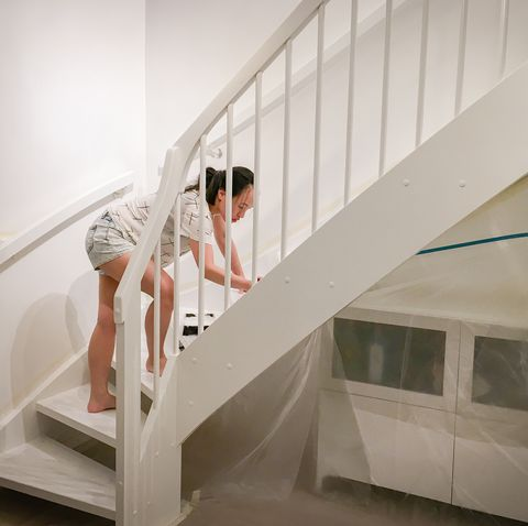 woman applying fresh white paint to the stairs