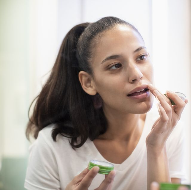Woman applying lip balm in mirror