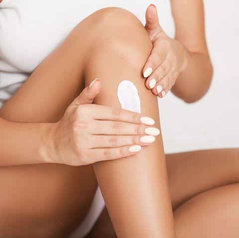 Woman applying moisturizer cream on her legs