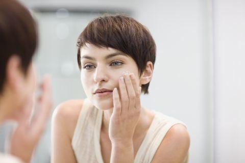 woman applying moisturizer in mirror