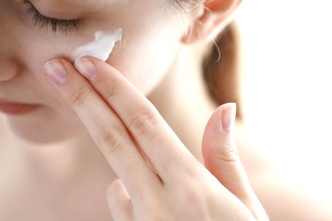 woman applying moisturizer on face