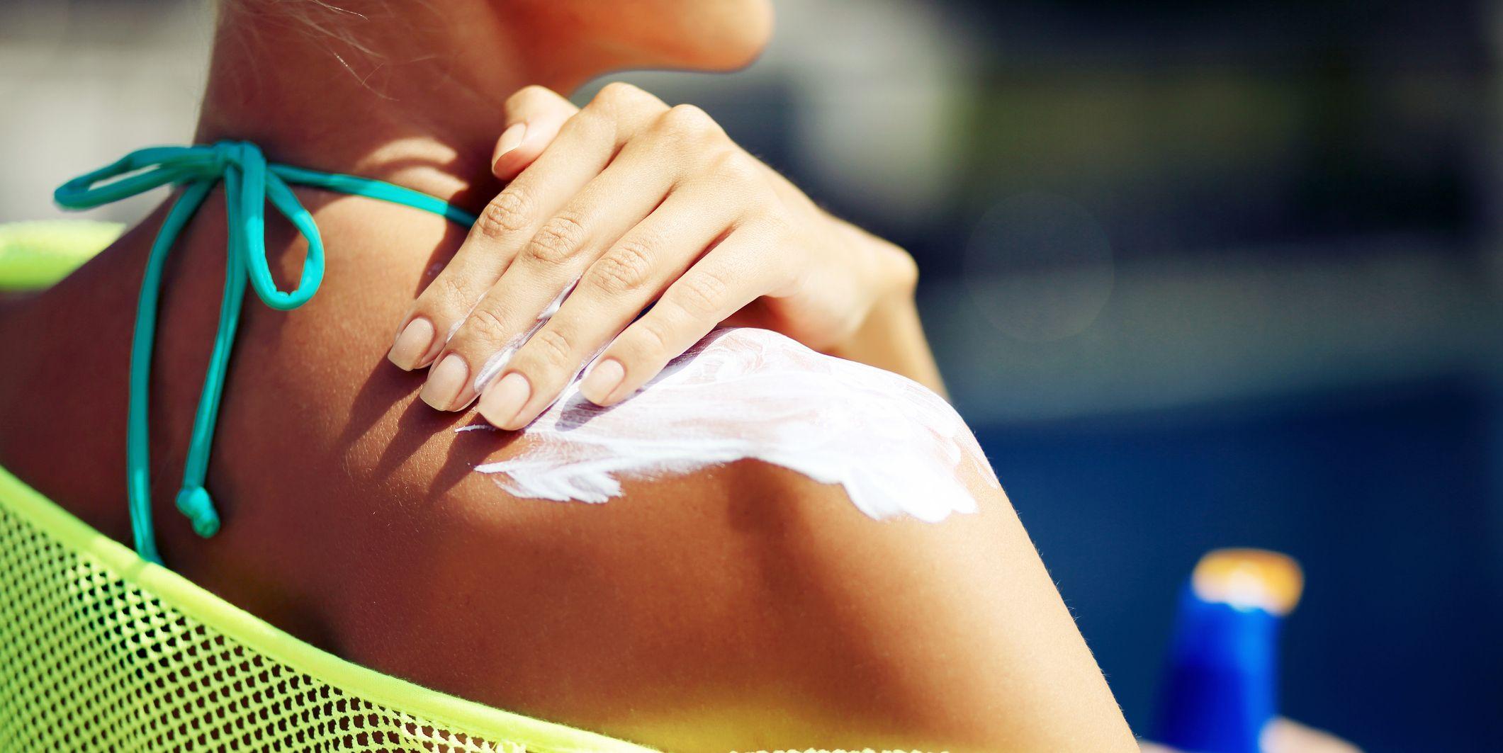Woman applying sunblock protection on shoulders