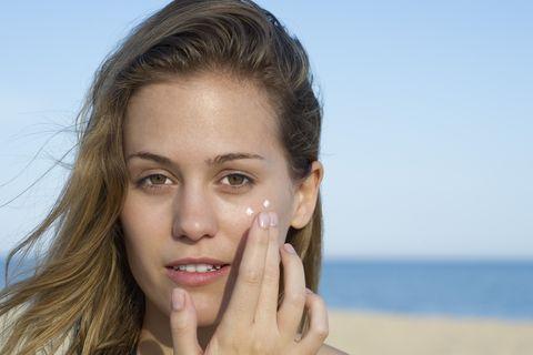 mujer se aplica crema en la cara al aire libre