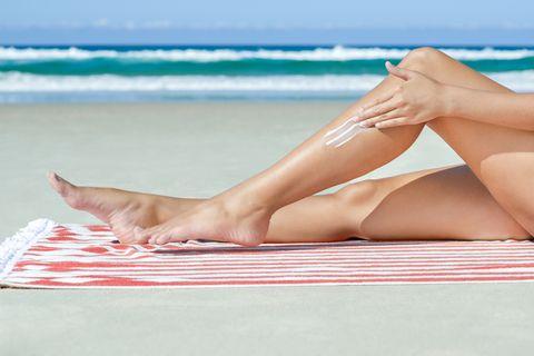 Woman applying sunscreen to legs.